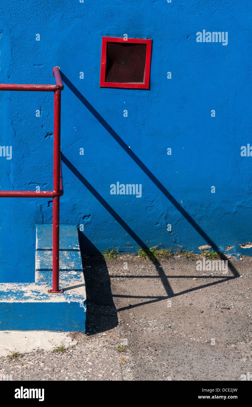 Red handrail blue wall - Stock Image