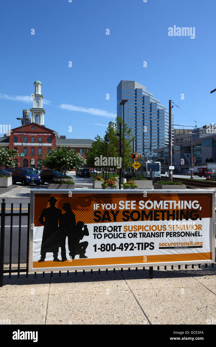 Sign encouraging people to report suspicious behaviour, Sports Legends Museum in left background, Baltimore, Maryland, - Stock Image