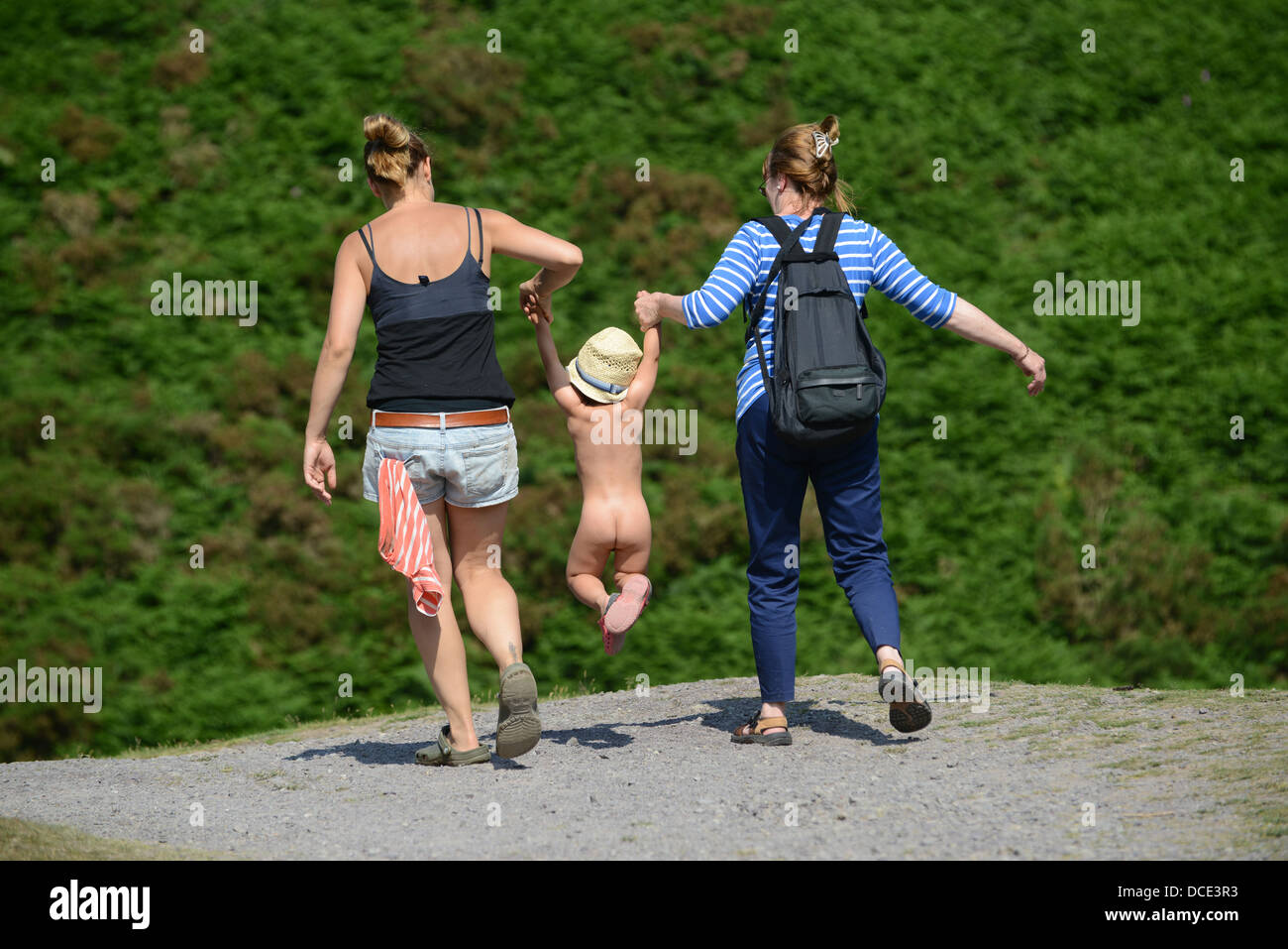 Two women carrying child by swinging the toddler by the arms on family day out. - Stock Image