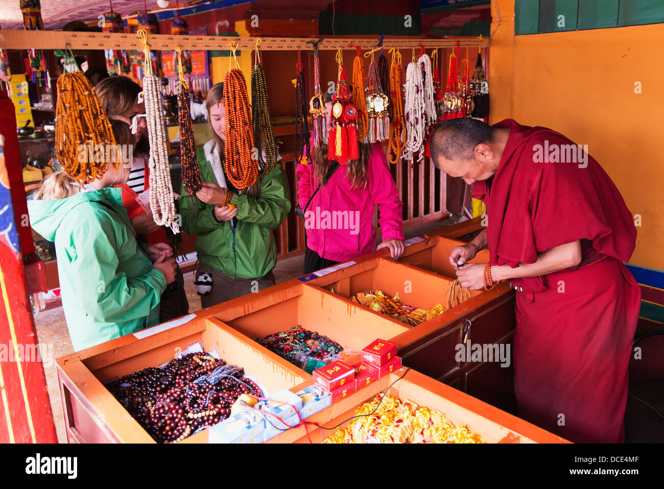 Tourists look at jewelry as monk works on some beaded jewelry at Drepung Monastery; Lhasa, Tibet, Xizang, China - Stock Image