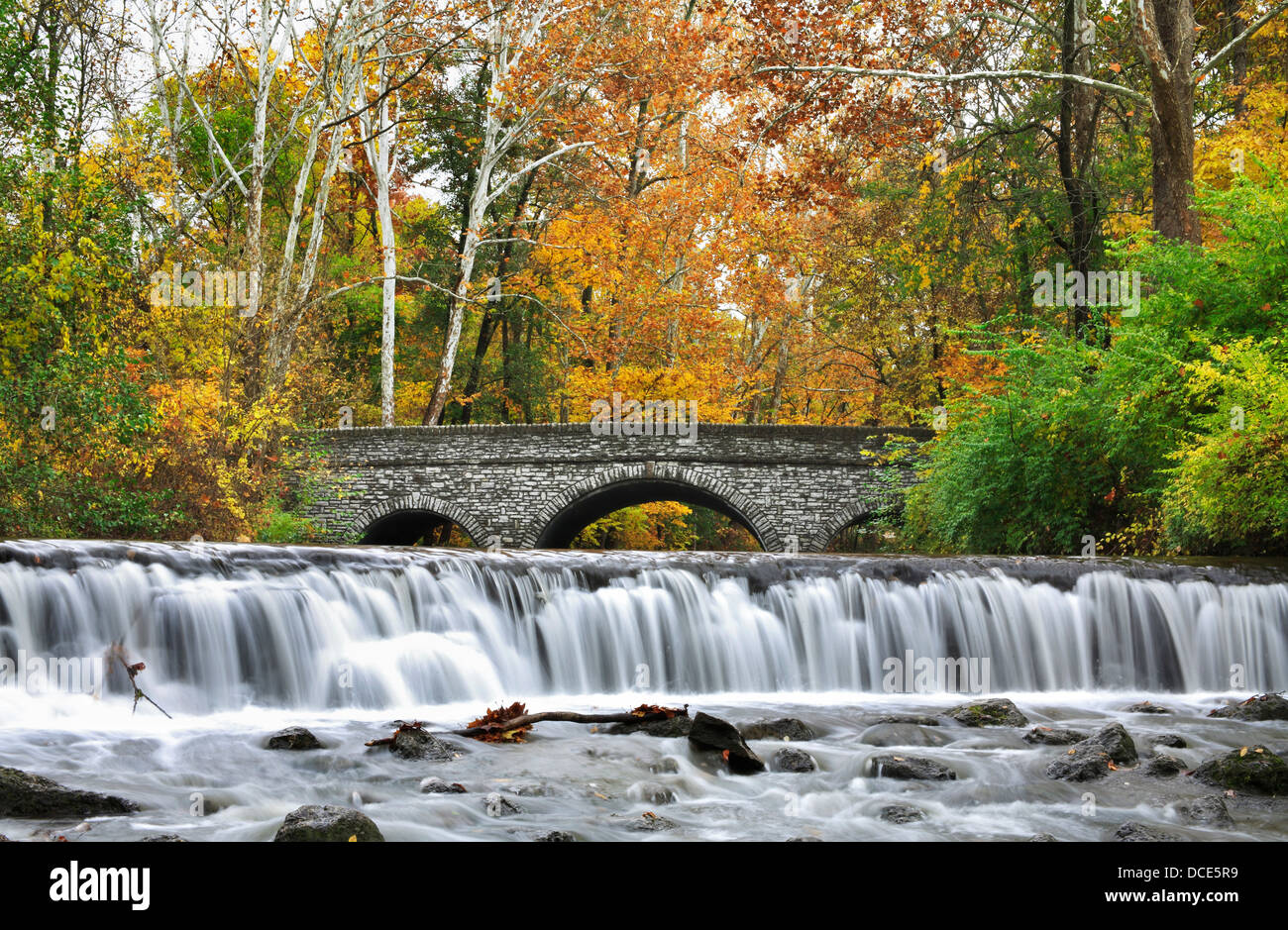 A Stone Bridge And Waterfall During Autumn In The Park, Sharon Woods, Southwestern Ohio, USA - Stock Image