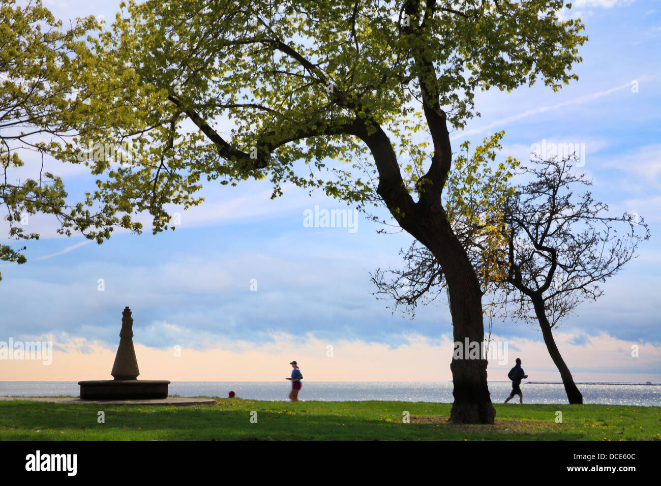 The Chicago Lakefront Trail And Joggers Framed By Foreground Trees With Lake Michigan In The Background, Chicago - Stock Image