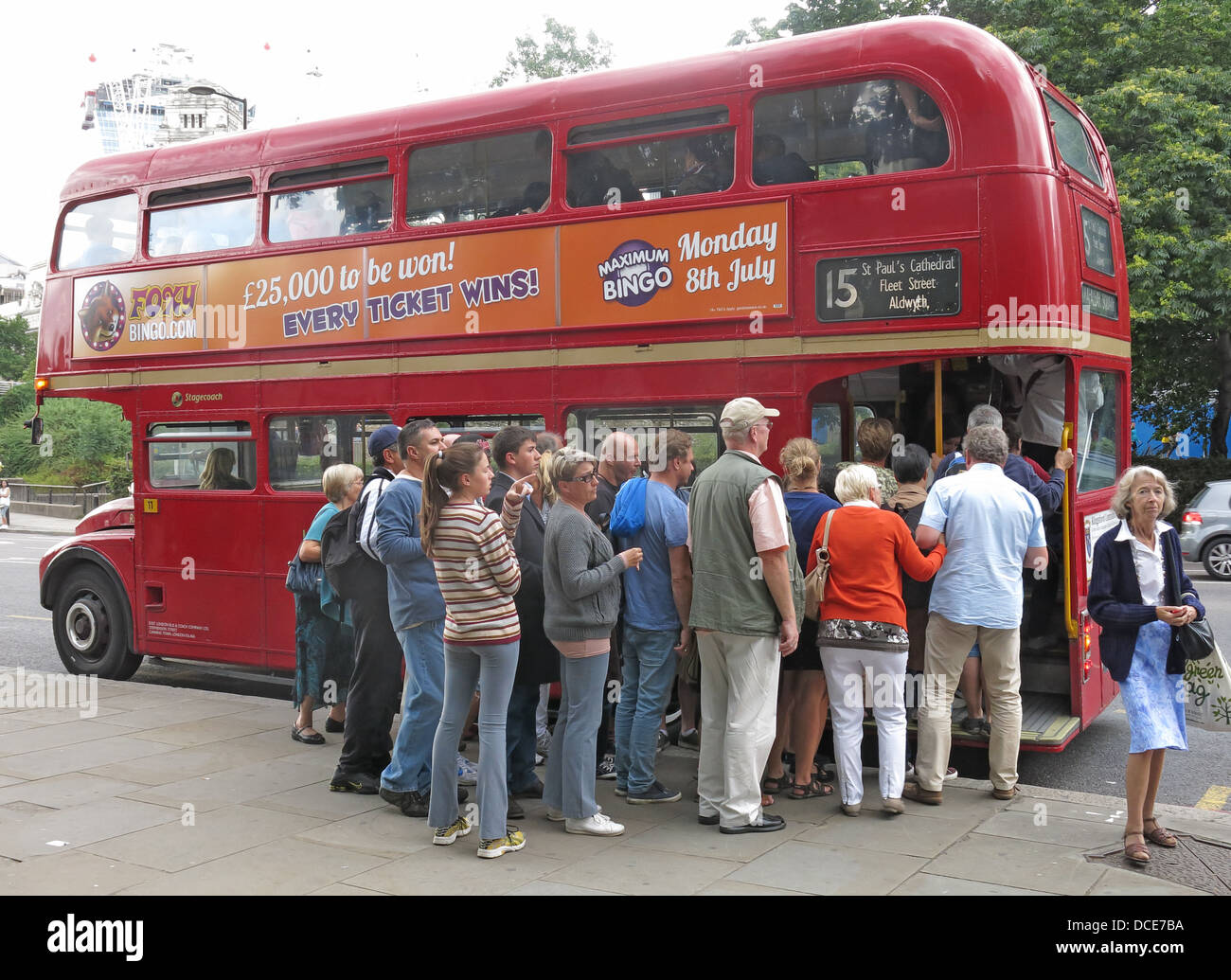 A group of tourists queuing to board a red London Routemaster bus , Great Britain Stock Photo