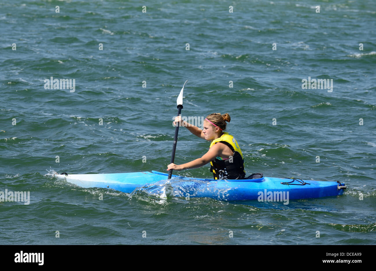 Teen girl on a kayak in a lake. - Stock Image