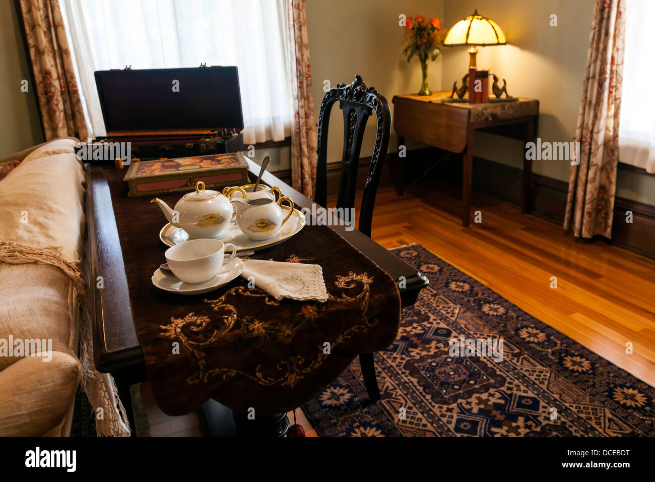Tea service set on sofa table in period sitting room with Persian rug. - Stock Image