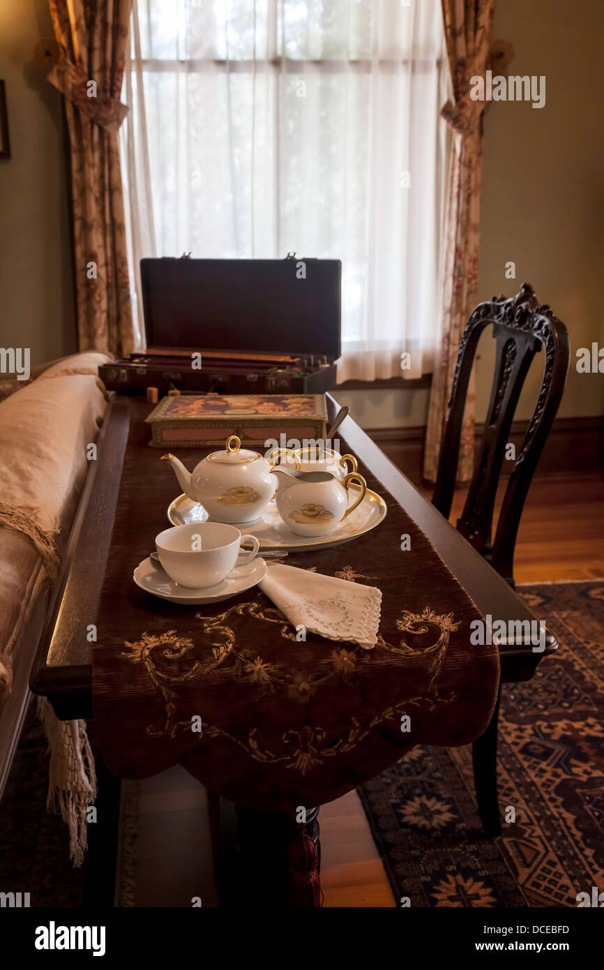 Tea service set on sofa table with table runner in period sitting room. - Stock Image