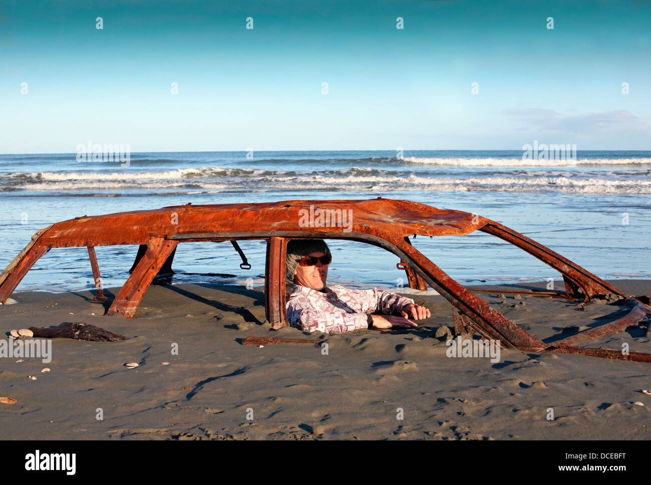 Man sits in rusted car wreck buried in sand on beach - Stock Image