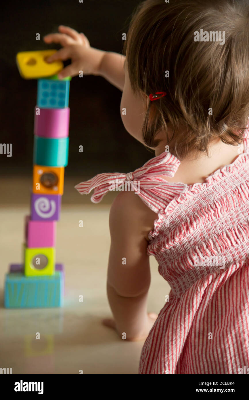 Baby girl skillfully balancing wooden blocks - Stock Image