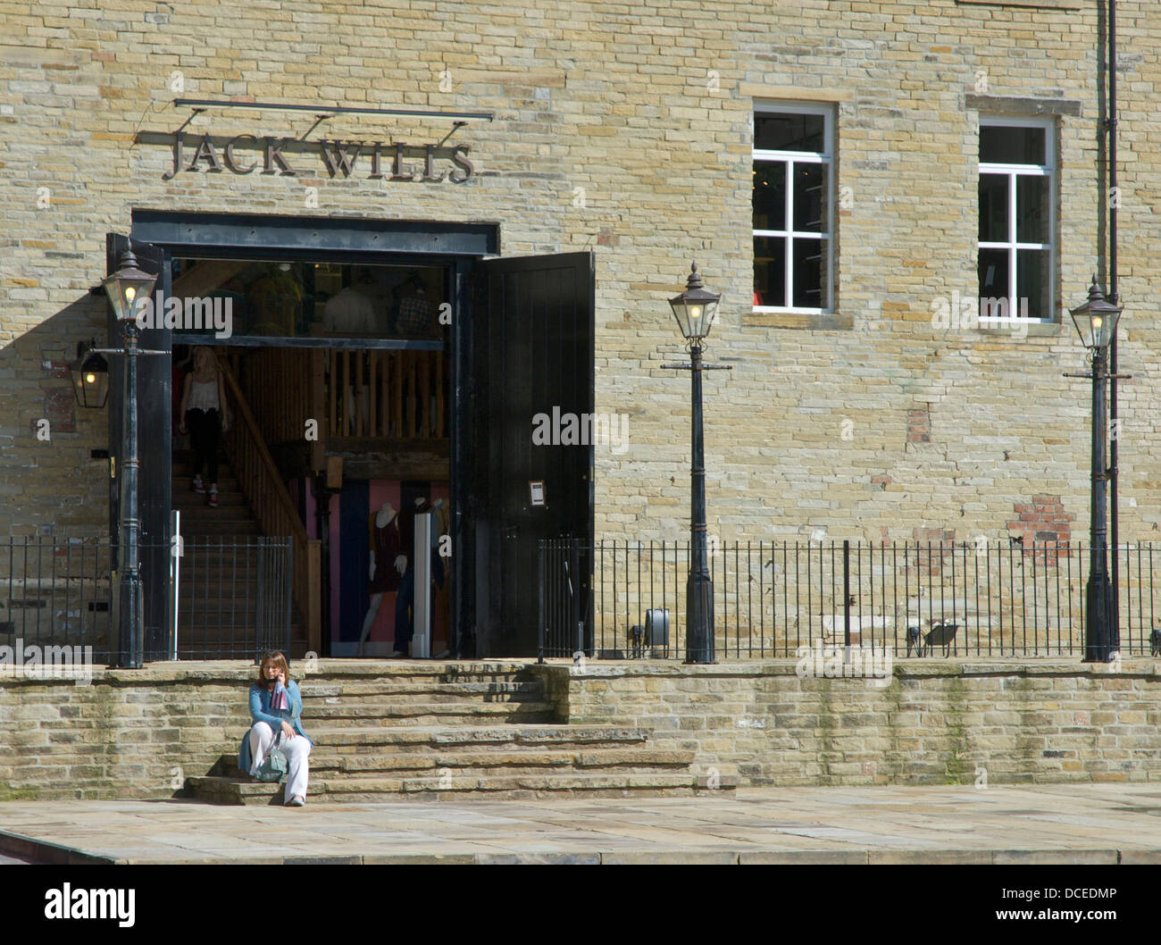 Woman sitting on steps outside Jack Wills shop, Dean Clough Mills, Halifax, West Yorkshire, England UK - Stock Image
