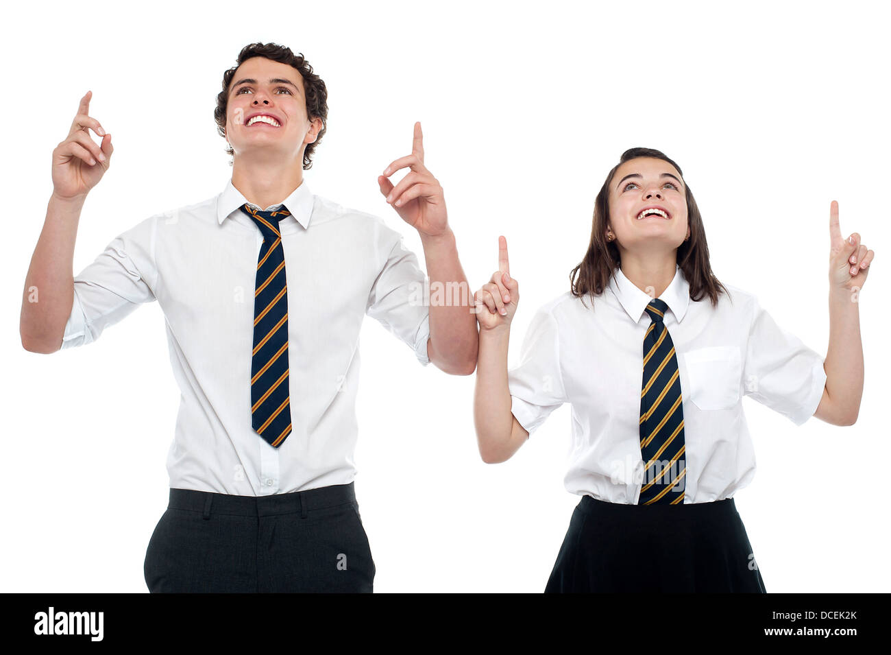 Schoolmates looking and pointing upwards. All on white background - Stock Image