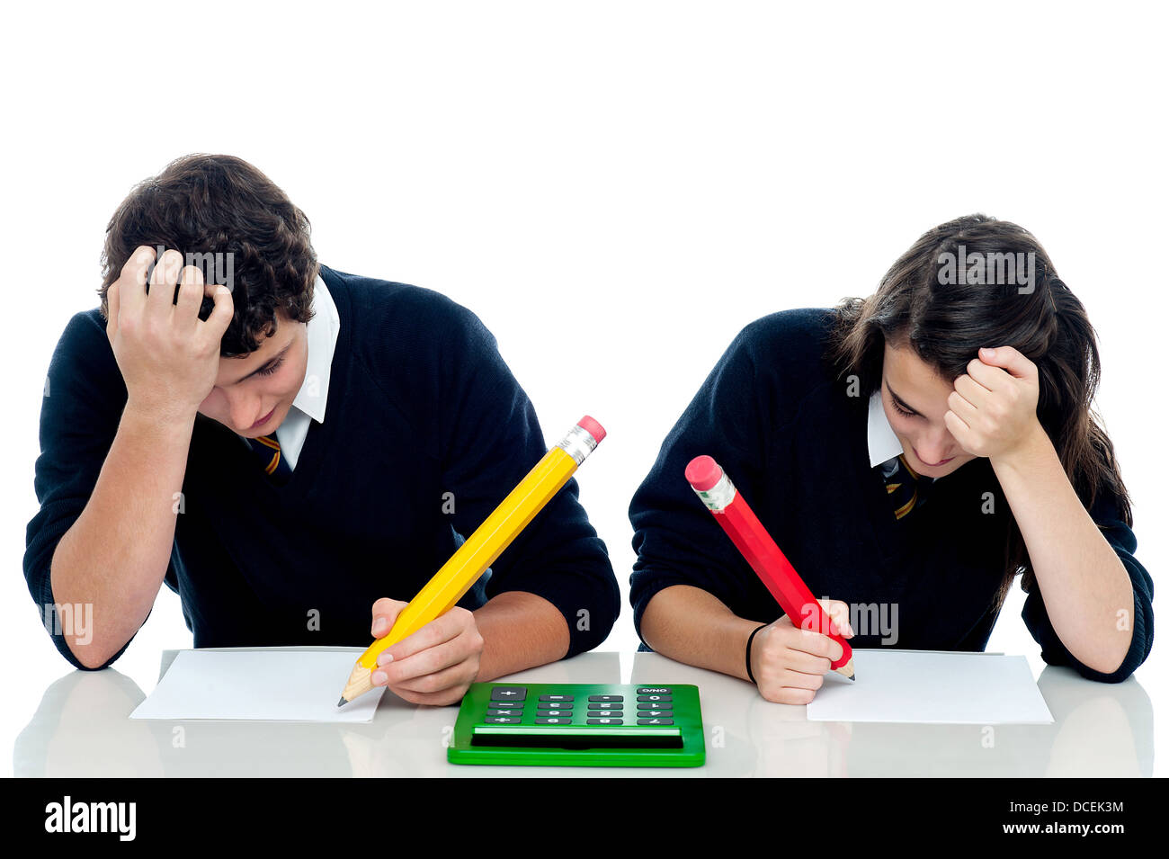 Students resting their arms on the desk, holding head and trying to recollect the answer - Stock Image