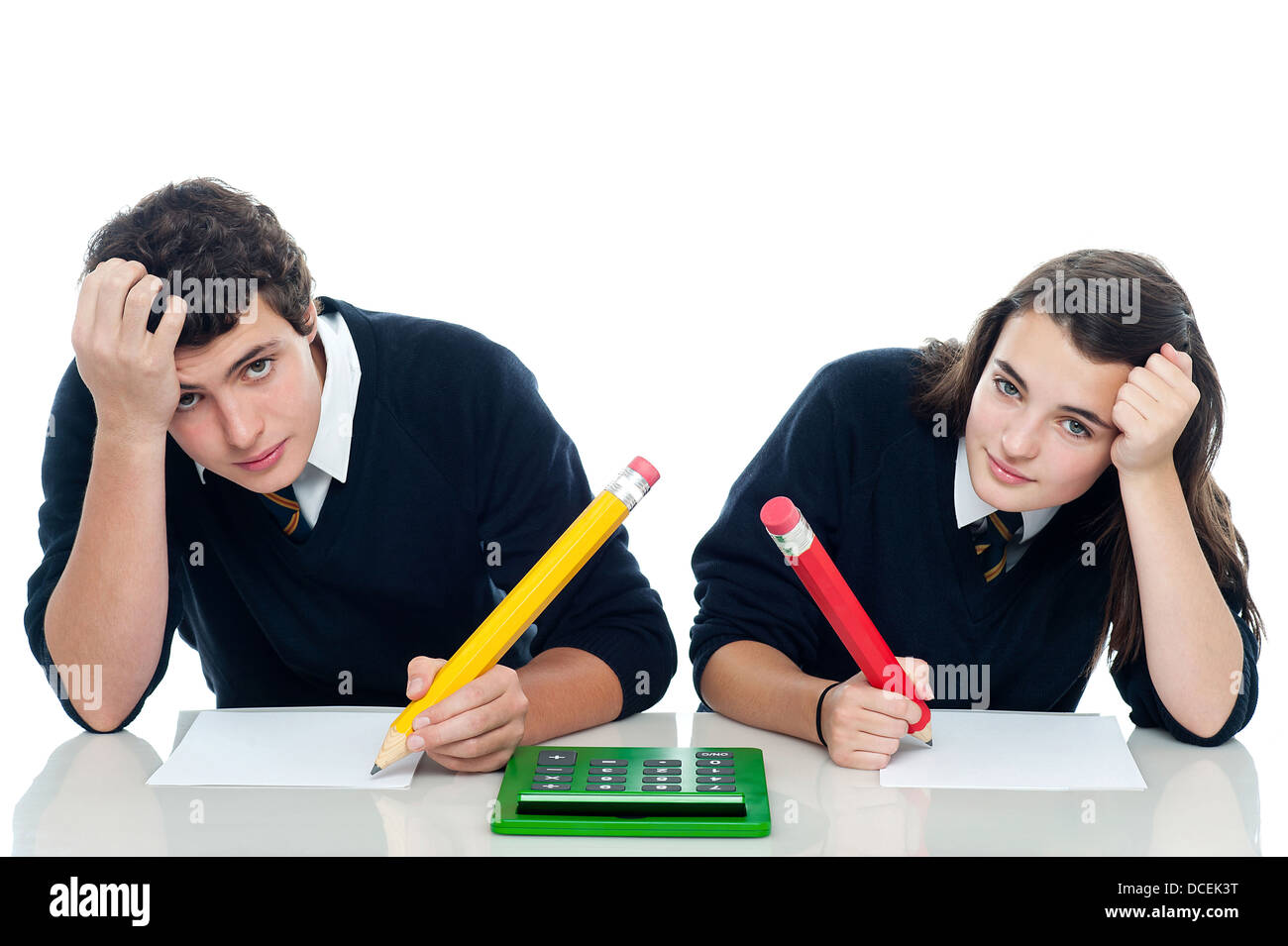 Confused students holding their heads during examination. Trying to recollect the answer - Stock Image