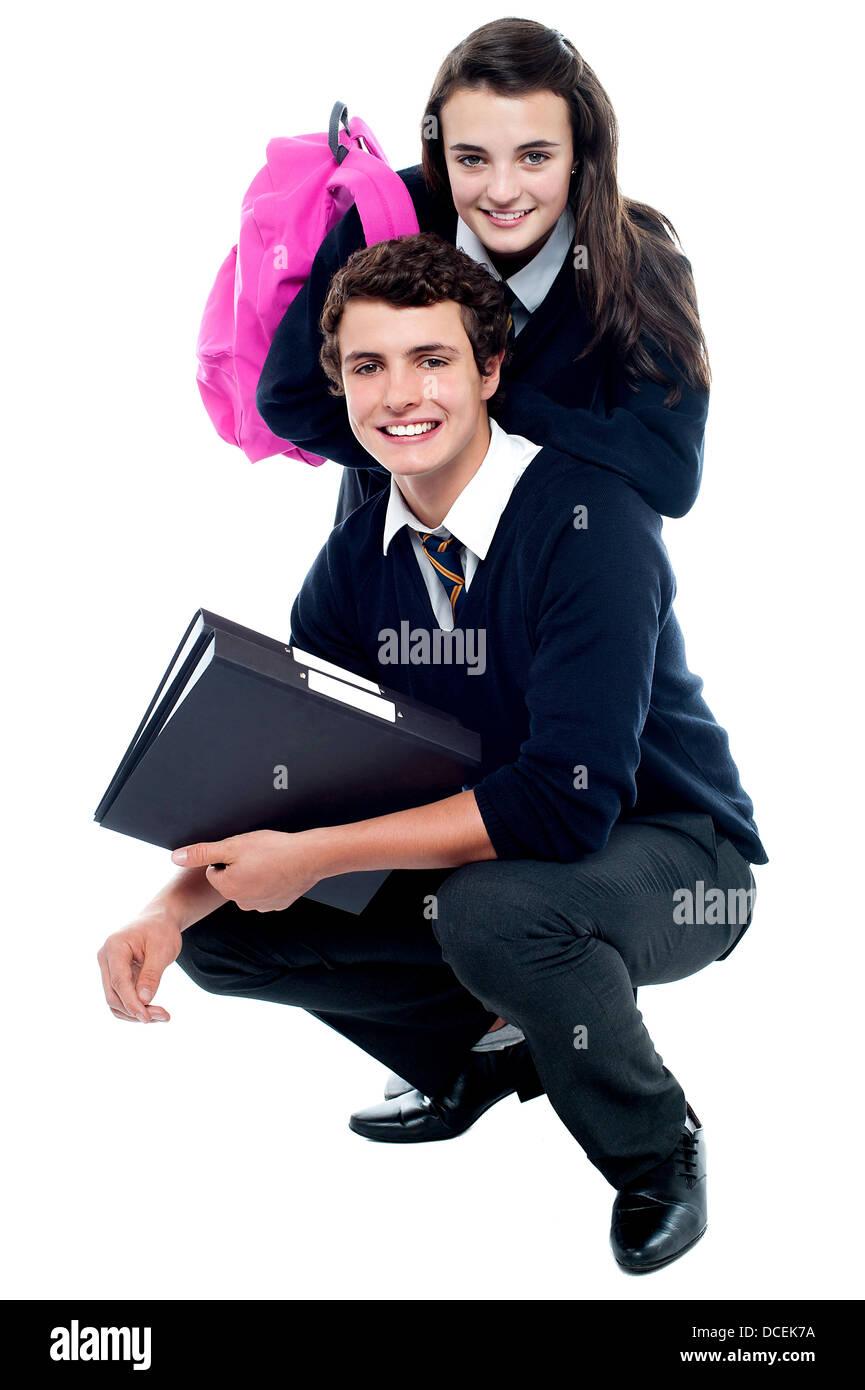Adorable schoolmates posing together happily, studio shot - Stock Image