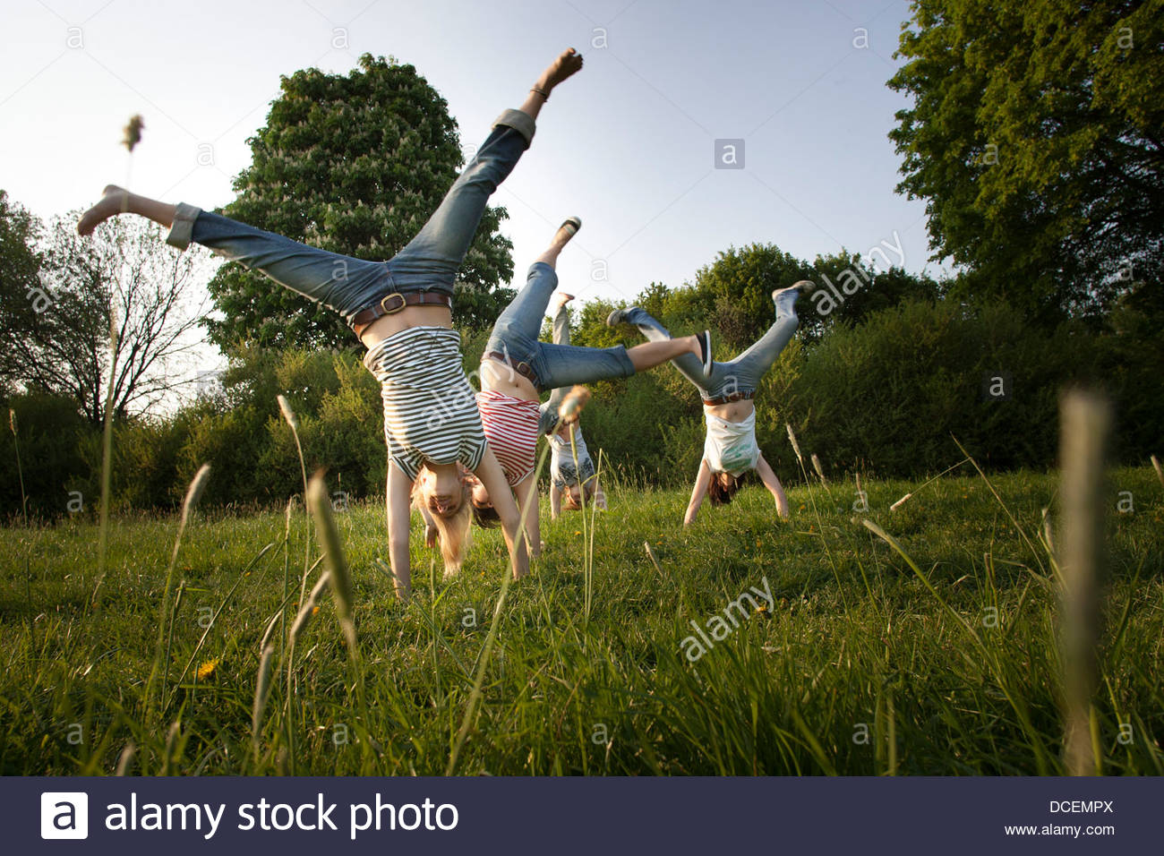 Female friends doing handstand in a garden - Stock Image