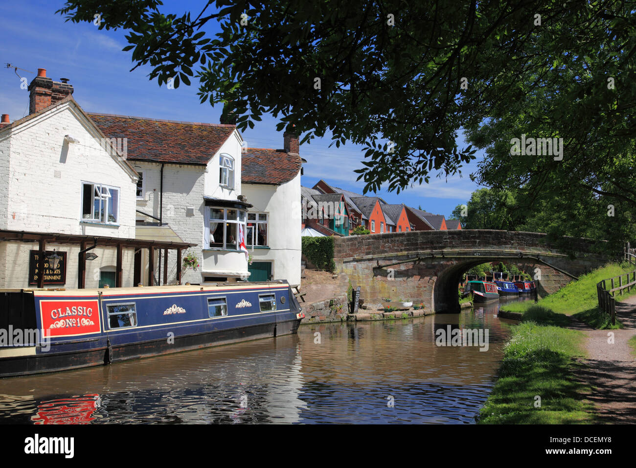 Narrowboats by the Boat Inn pub at Gnosall in Staffordshire next to Gnosall Bridge on the Shropshire Union Canal - Stock Image