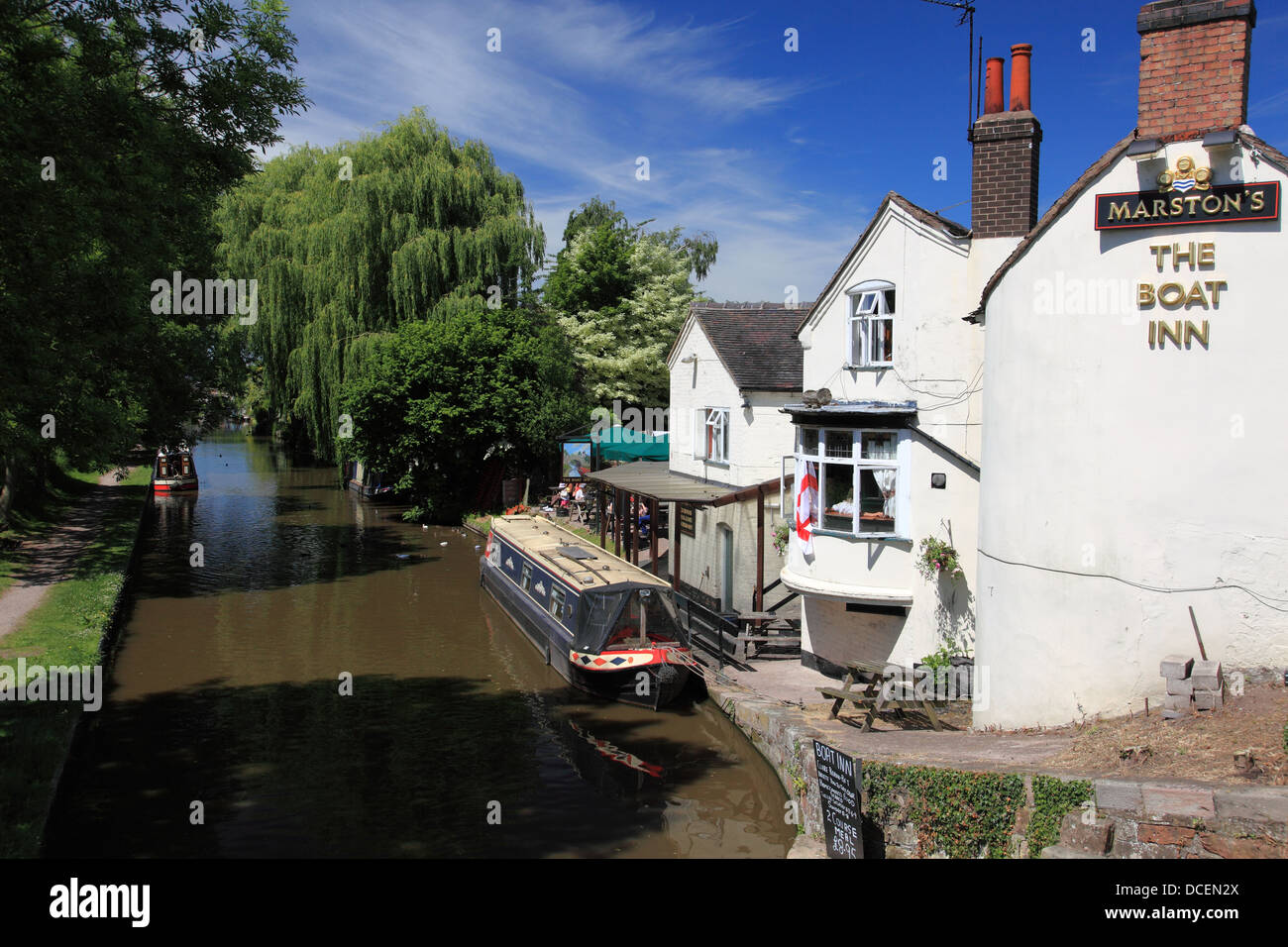 A narrowboat by the Boat Inn pub seen from Gnosall Bridge in Staffordshire on the Shropshire Union Canal - Stock Image