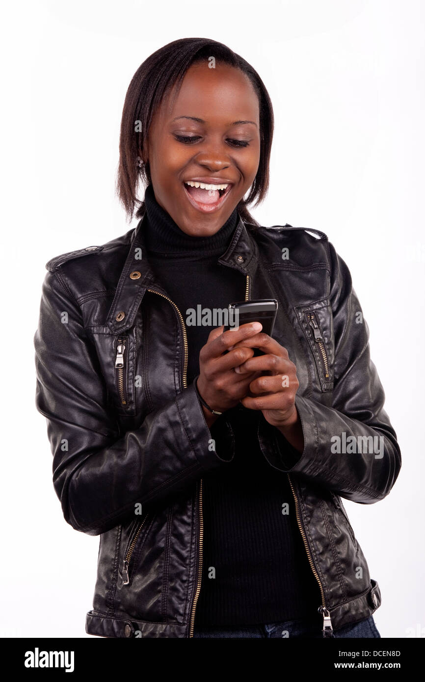 Gorgeous young South African woman reading a surprising message on her phone. - Stock Image