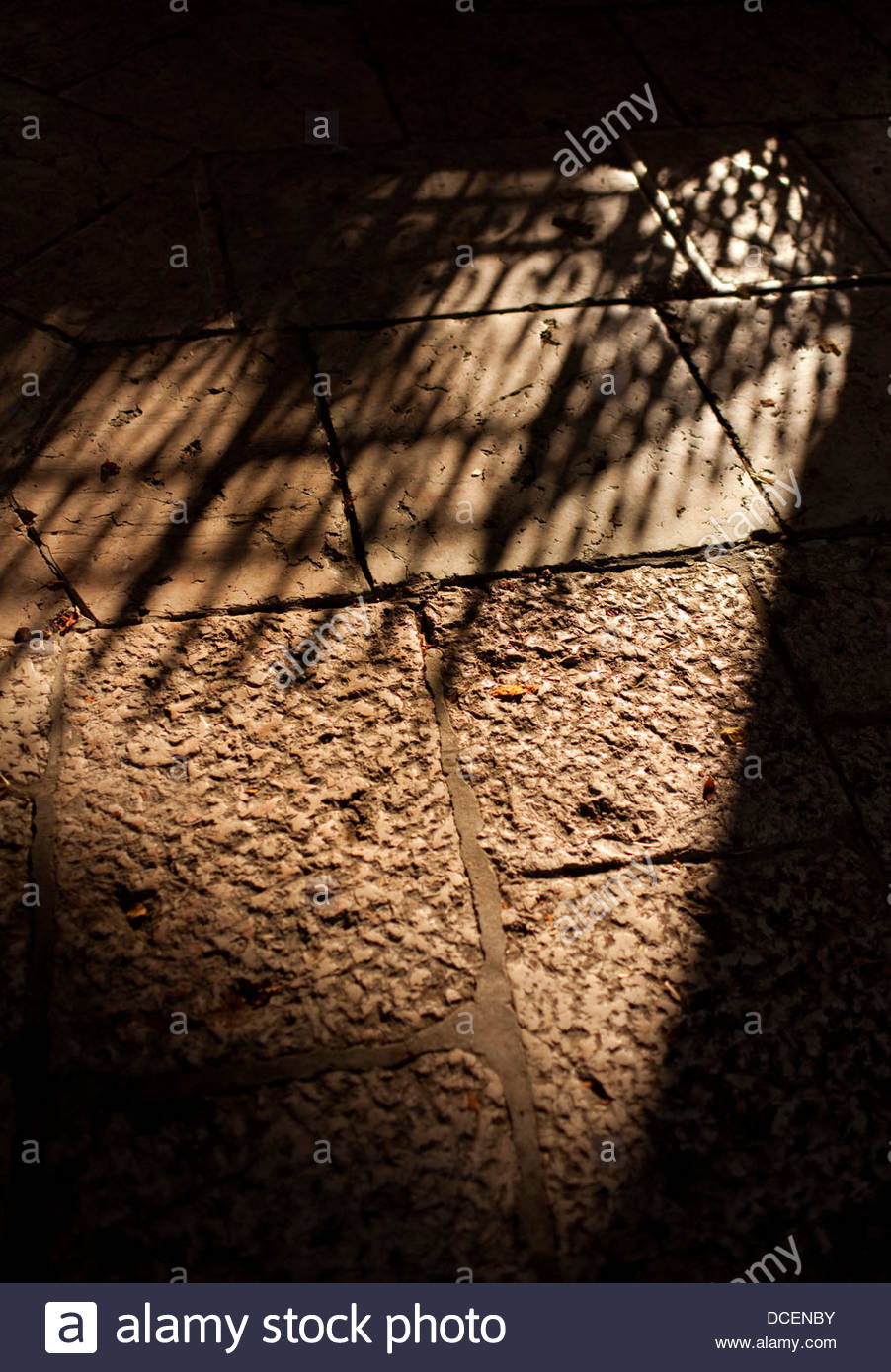 Shadow of a gate on floor - Stock Image