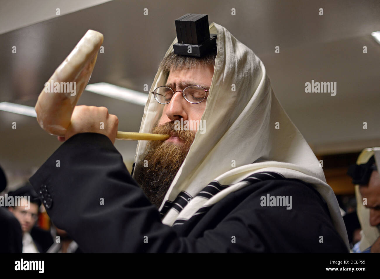 Religious Jewish man blows a shofar during services prior to New Year in Lubavitch headquarters in Crown Heights, - Stock Image