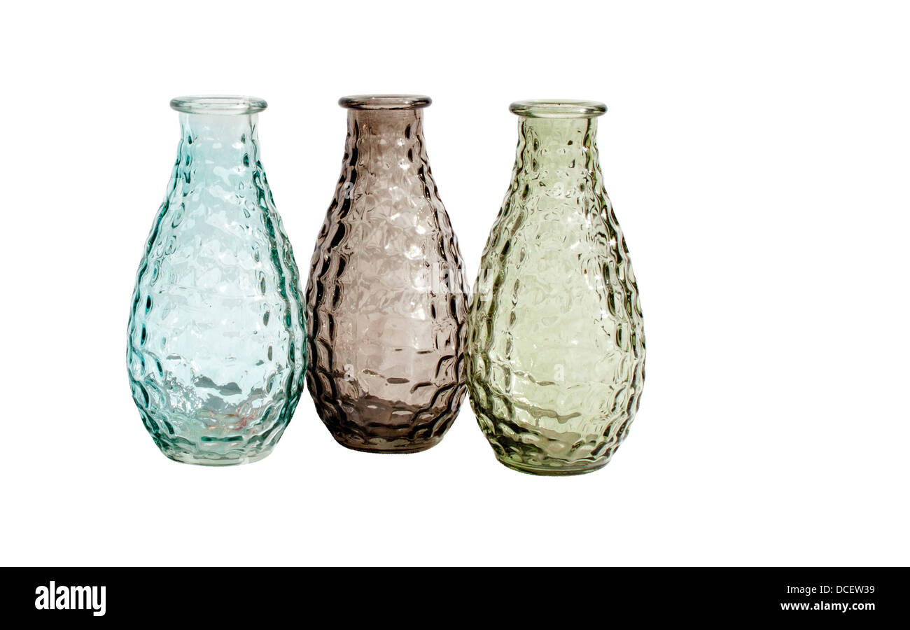 A set of three differently colored transparent glass vases on an isolated white background - Stock Image