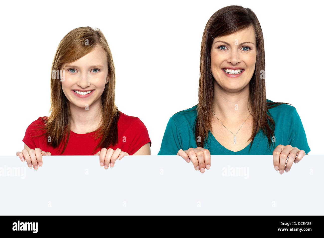 Cheerful young product promoters holding blank white billboard. - Stock Image