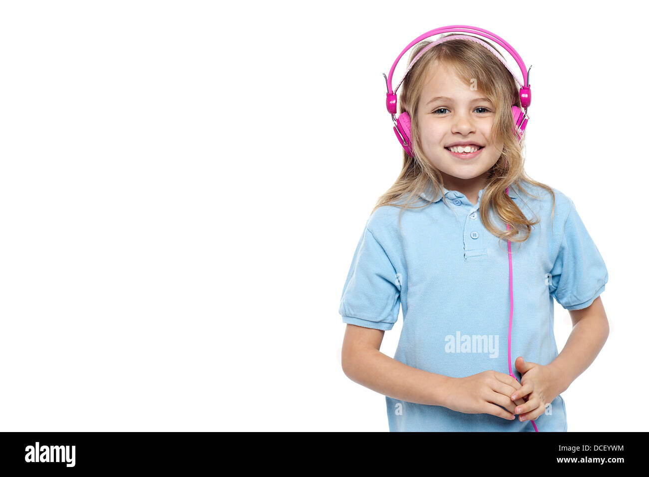 Half length portrait of a sweet little girl with headphones on. All on white. - Stock Image