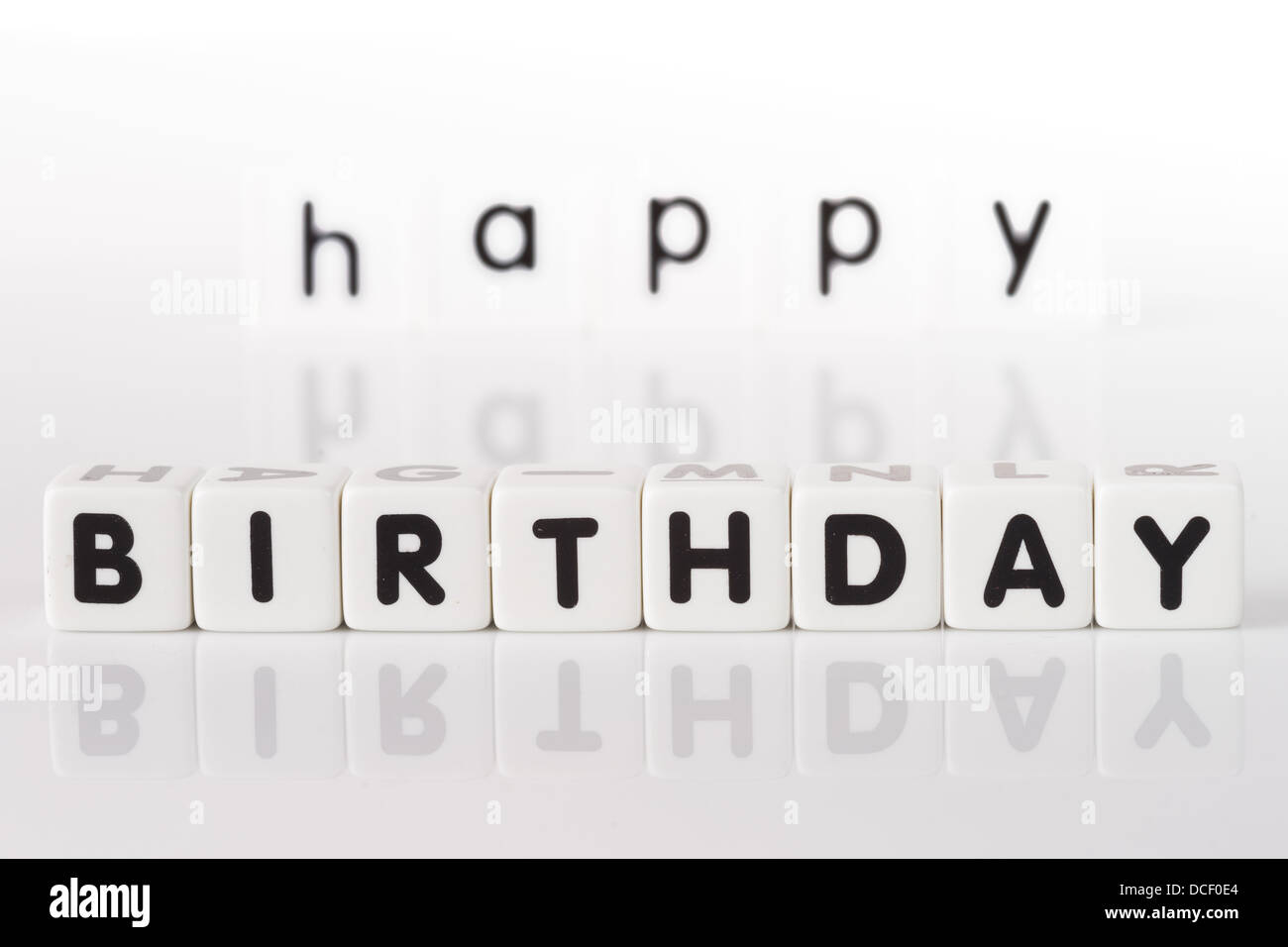 Happy Birthday spelled in game letters with reflection isolated on white background - Stock Image
