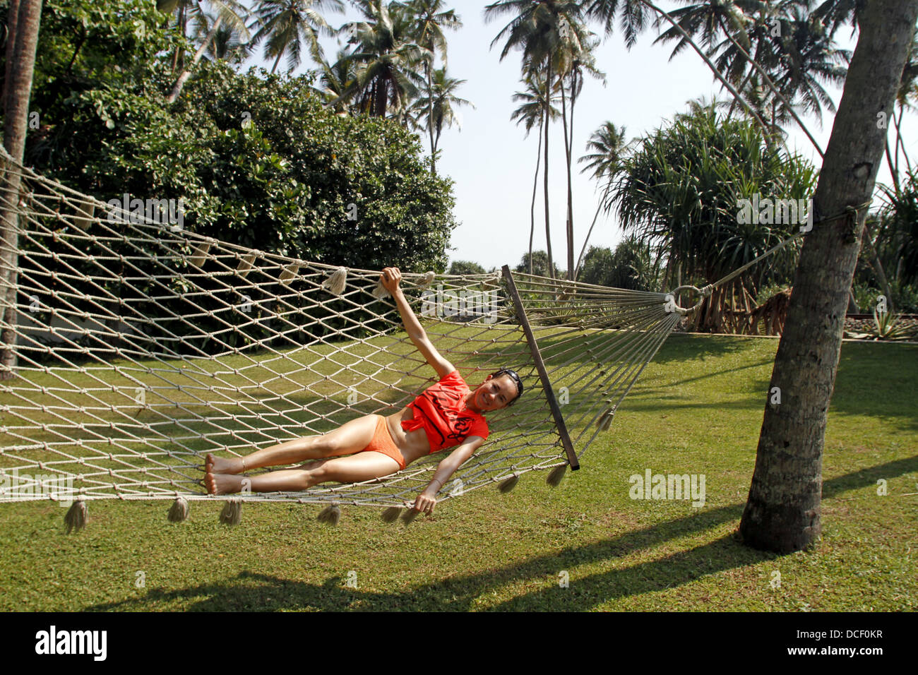 WOMAN ON ROPE HAMMOCK BENTOTA BEACH SRI LANKA 14 March 2013 - Stock Image
