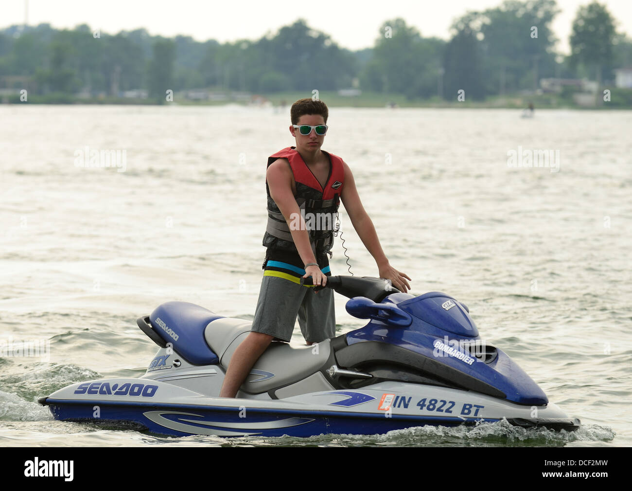 Teen boy on a personal watercraft. - Stock Image