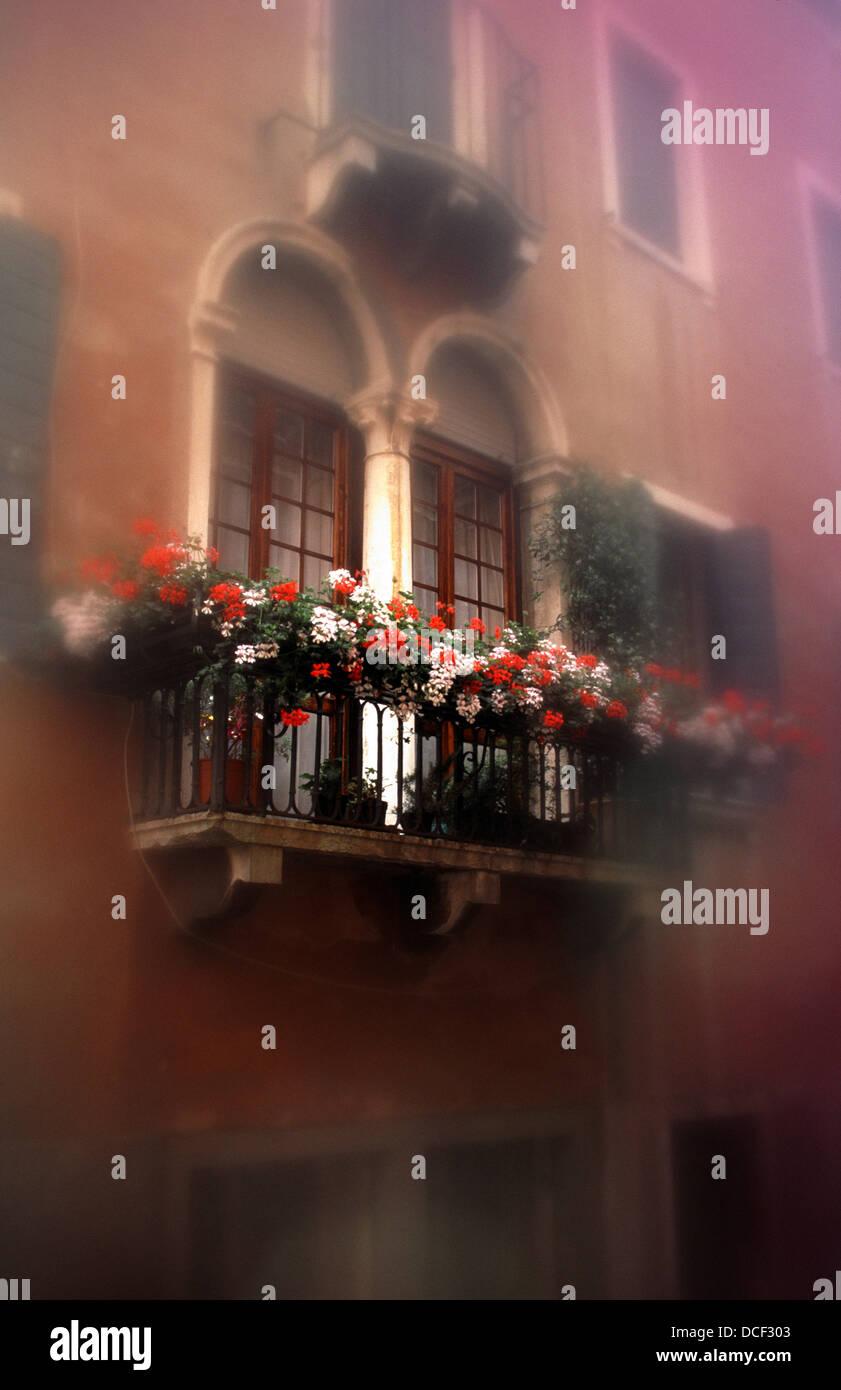 Venice-Impression: Balcony with arched doors; Venedig-Impression: Rundbogentüren hinter Blumenbalkon - Stock Image