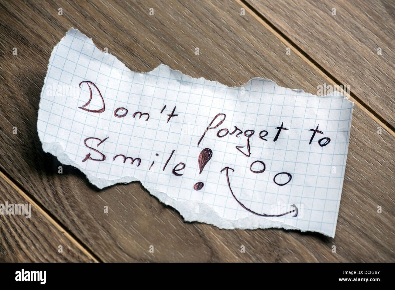 Don't forget to Smile - Hand writing text on a piece of paper on wood background - Stock Image