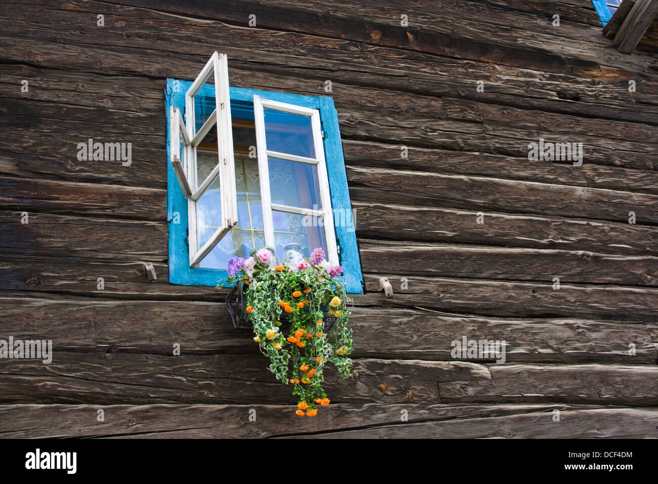 offenes Fenster in einem alten Holzhaus; open window of an old alpine log house - Stock Image