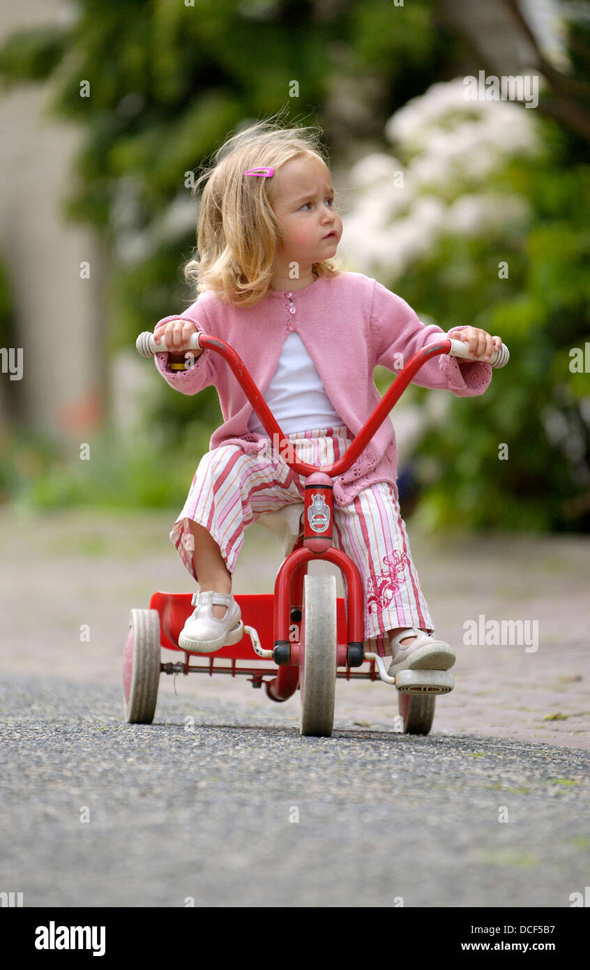 Little girl on a tricycle in the street - Stock Image