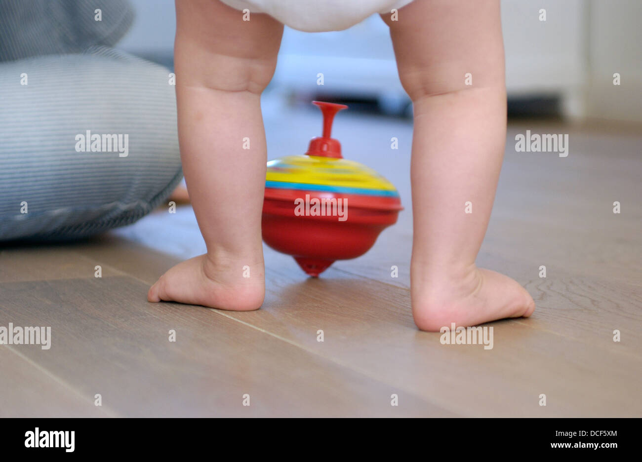 Toddlers feet and a humming top - Stock Image