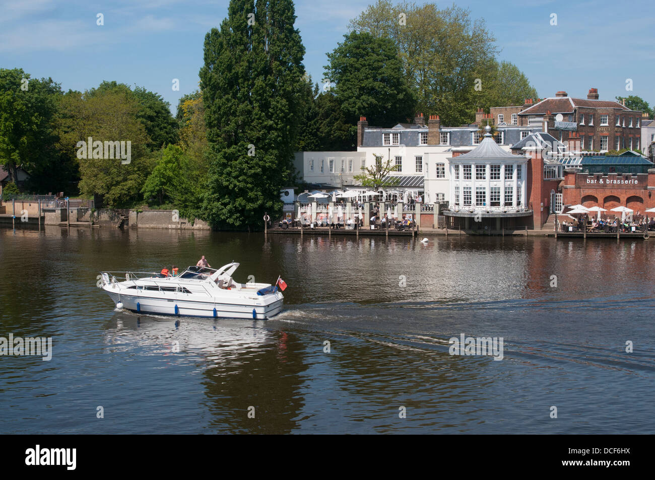 Boat on River Thames at Hampton Court, East Molesey in Middlesex with a view over the River's Edge Bar and Brasserie - Stock Image