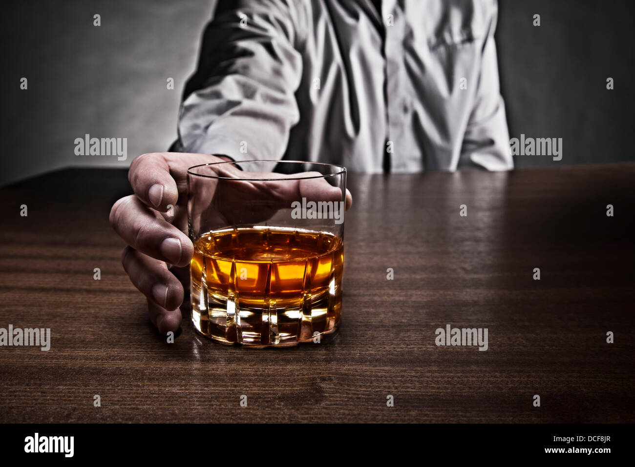 Hand of a man reaching for a glass of whiskey, which stands on a table. Stock Photo