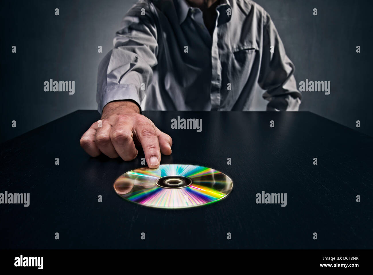 Man pushing a CD with data on a table, symbolizing the passing of secret data. - Stock Image