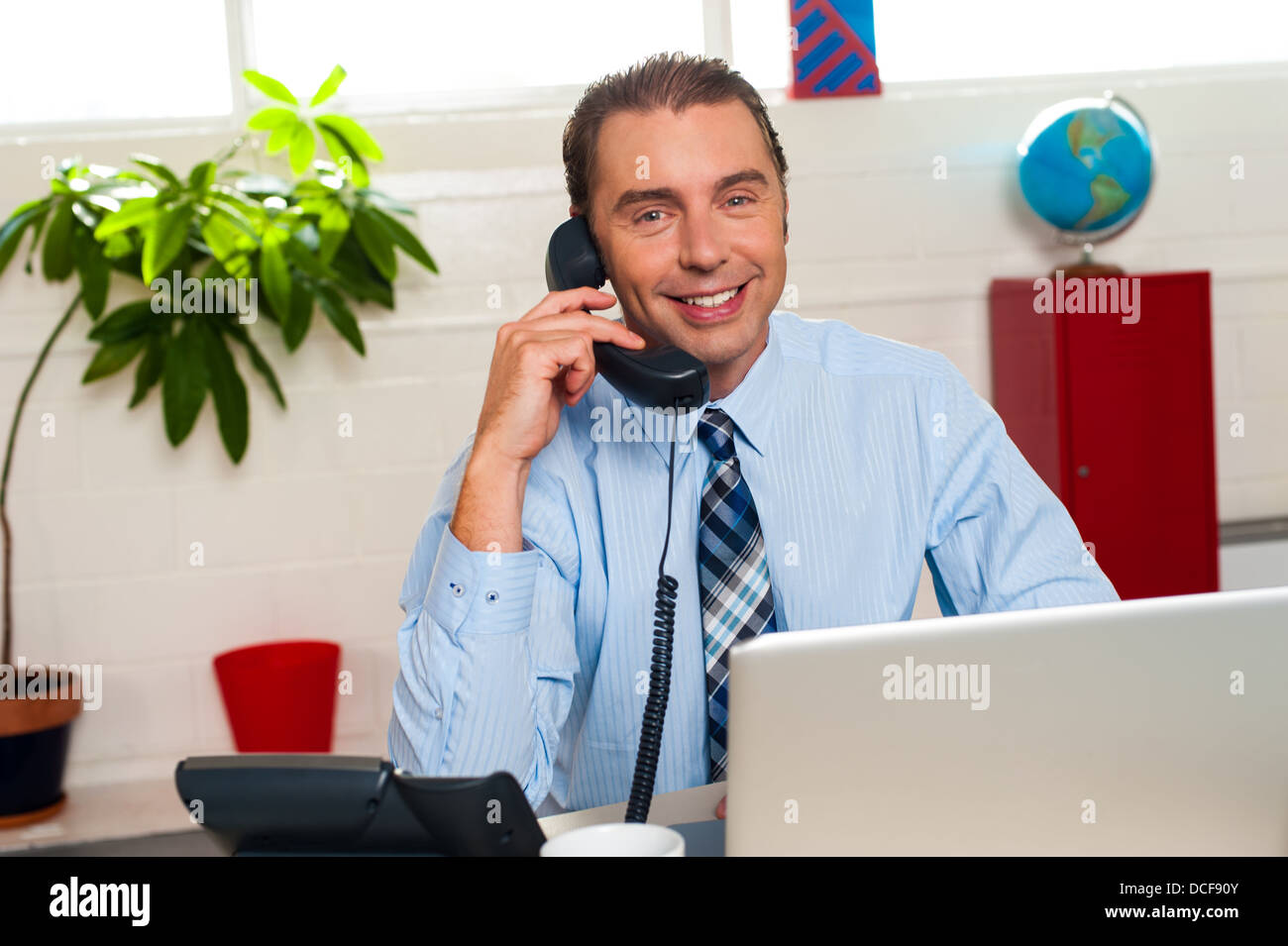 Smiling manager engaged in business interactions over a phone call. - Stock Image