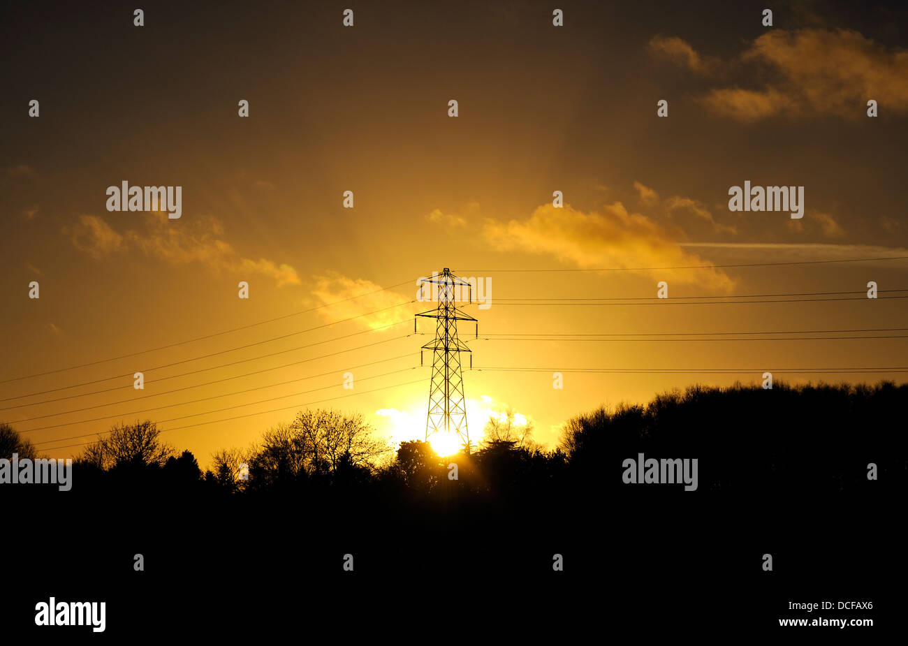 SETTING SUN BEHIND ELECTRICITY PYLON SOLAR POWER - Stock Image