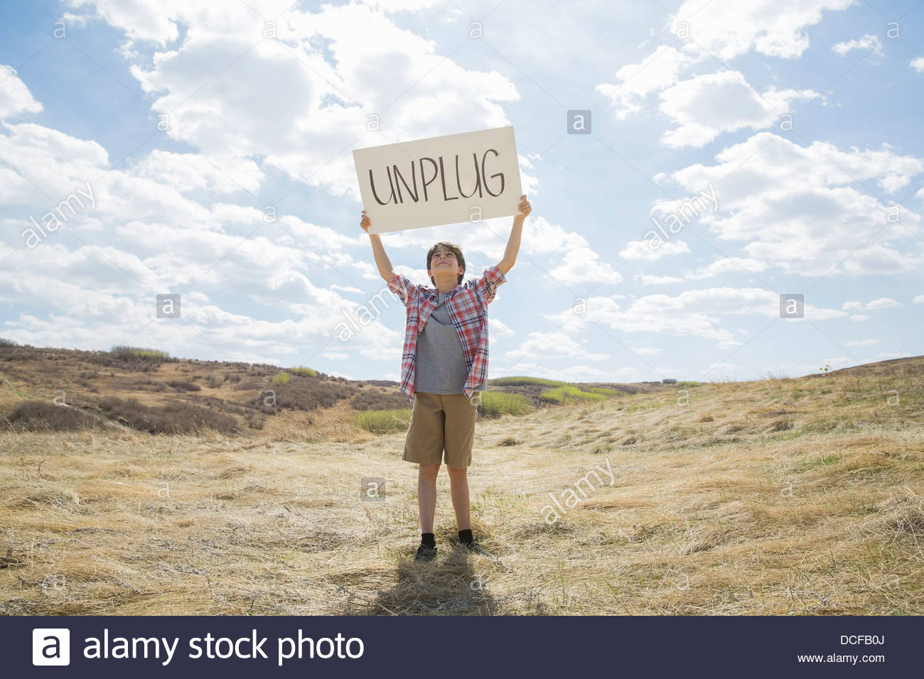 Portrait of little boy holding unplug sign outdoors - Stock Image