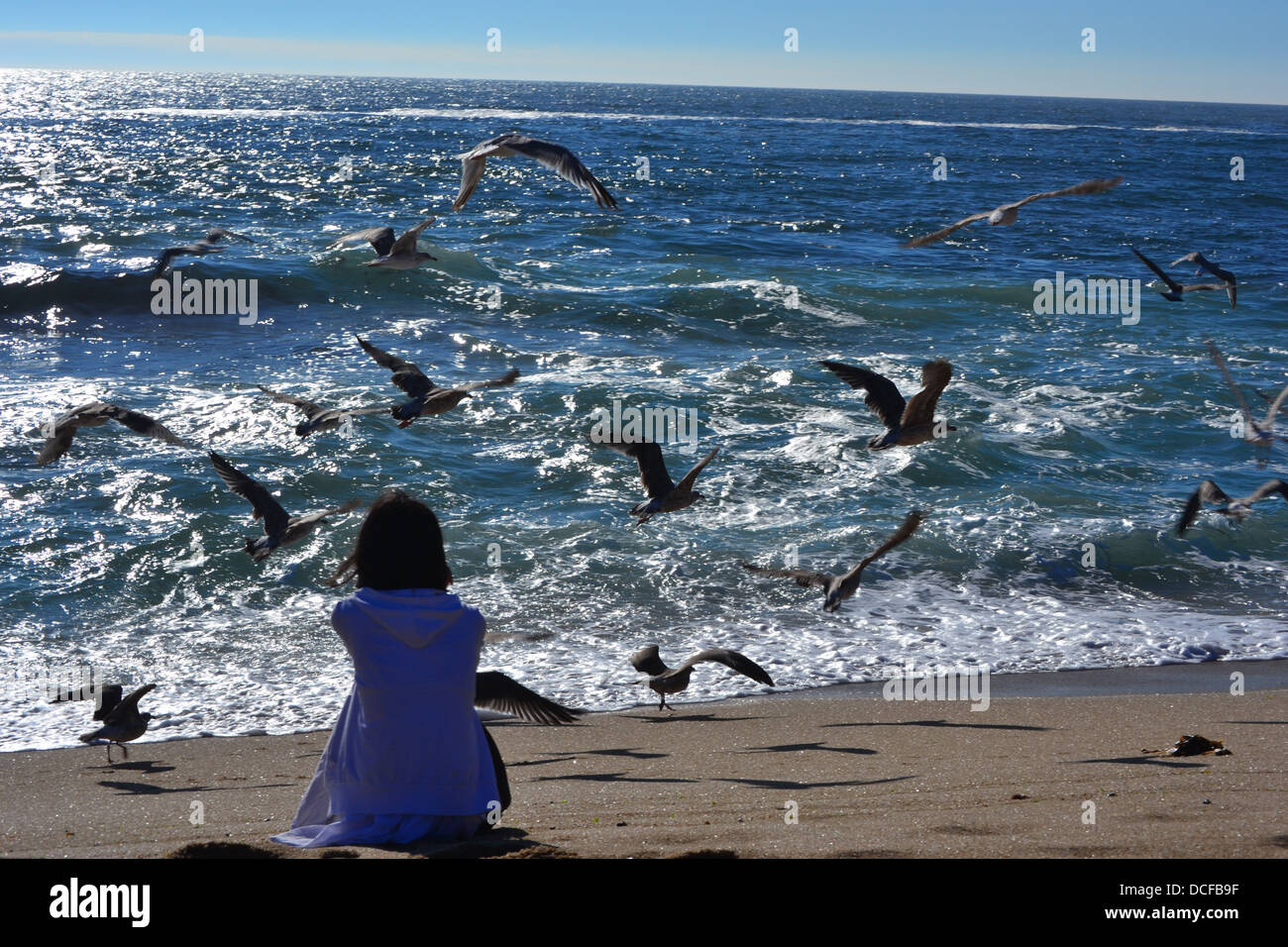 a girl sitting on the beach alone facing the sea with ...