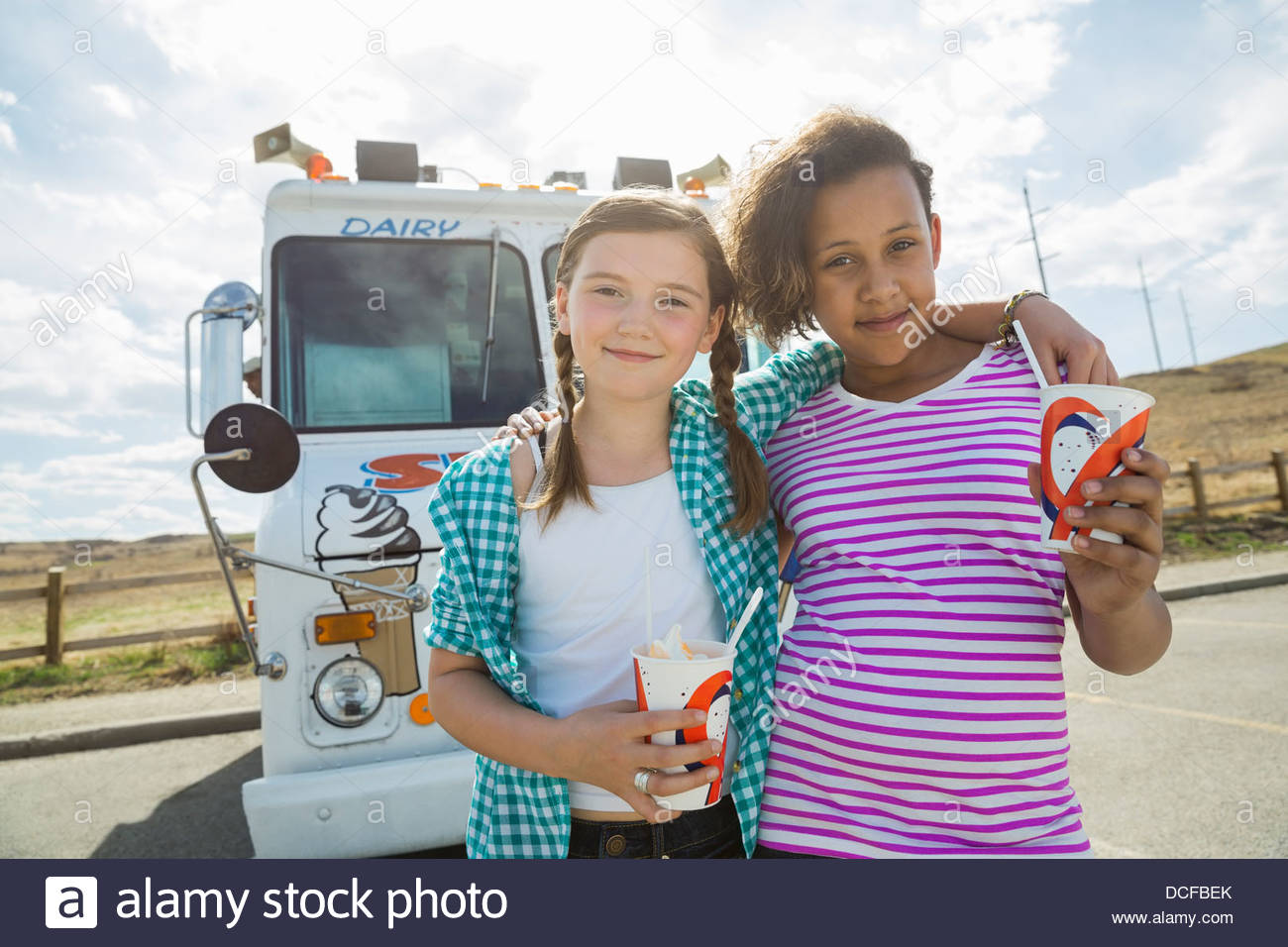 Portrait of girls holding ice cream cups outdoors - Stock Image