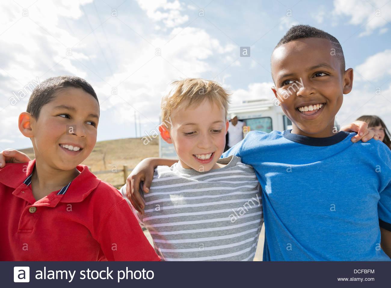 Boys standing outside with arms around each other Stock Photo