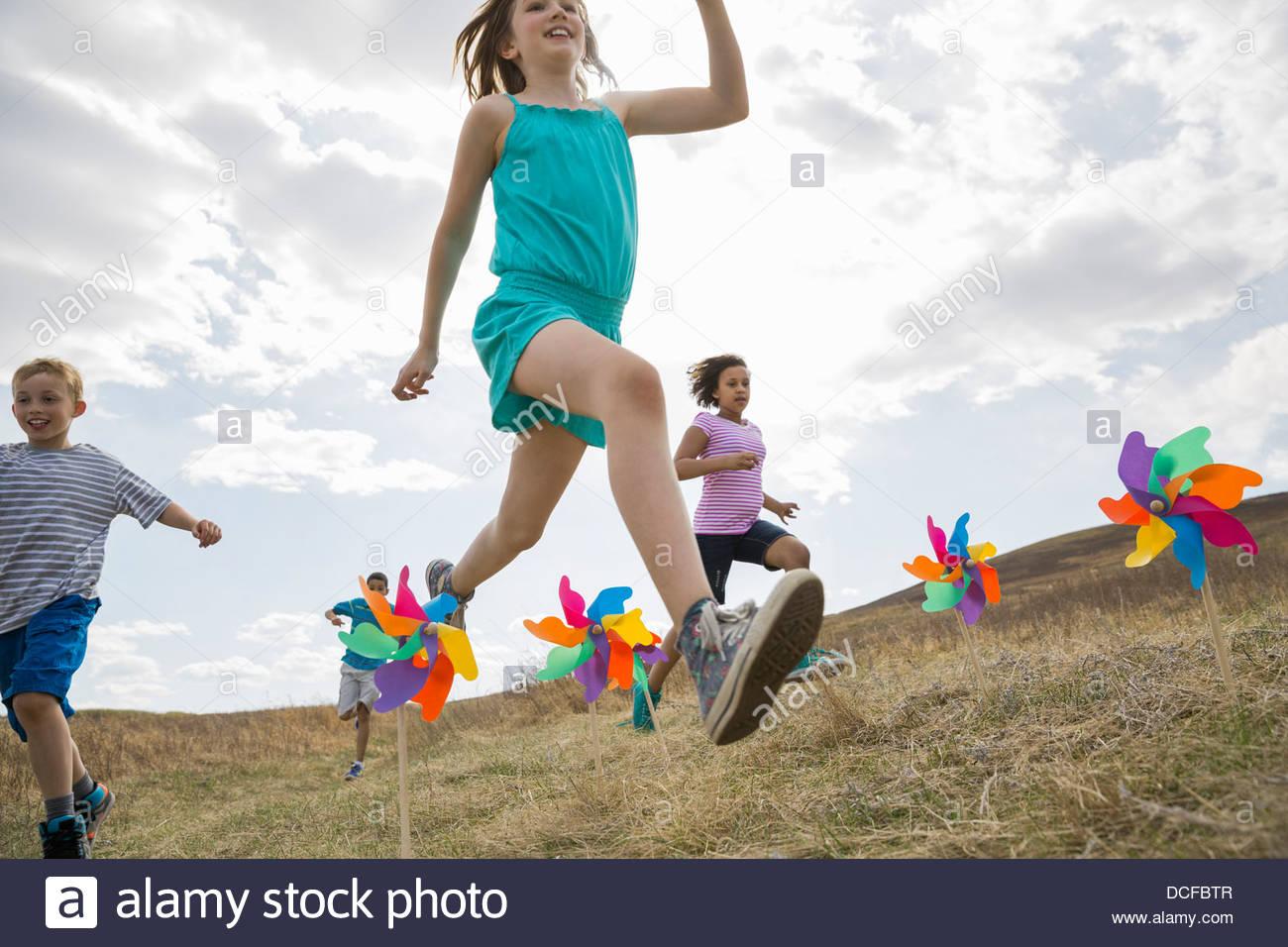 Schoolchildren jumping over pinwheels in field - Stock Image