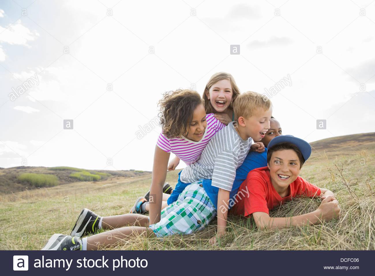 Playful schoolchildren playing outdoors - Stock Image