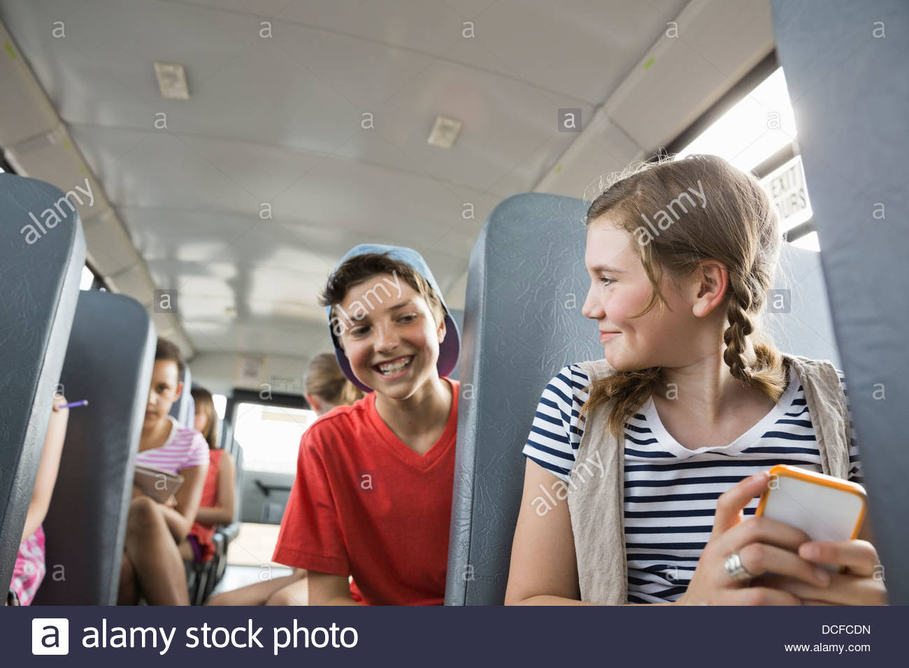 Girl hiding mobile phone from friend inside school bus - Stock Image