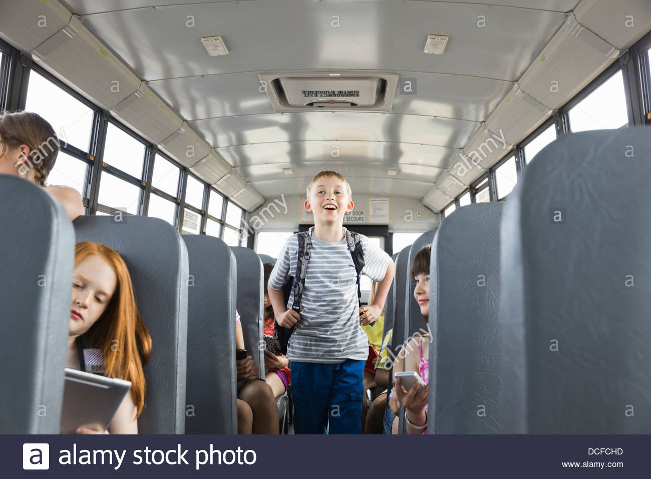 Cheerful schoolboy standing in aisle of bus - Stock Image