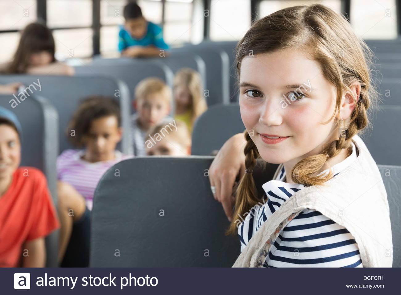 Portrait of cute girl inside school bus - Stock Image
