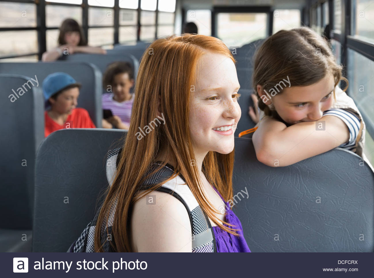 Schoolgirls looking out bus window - Stock Image