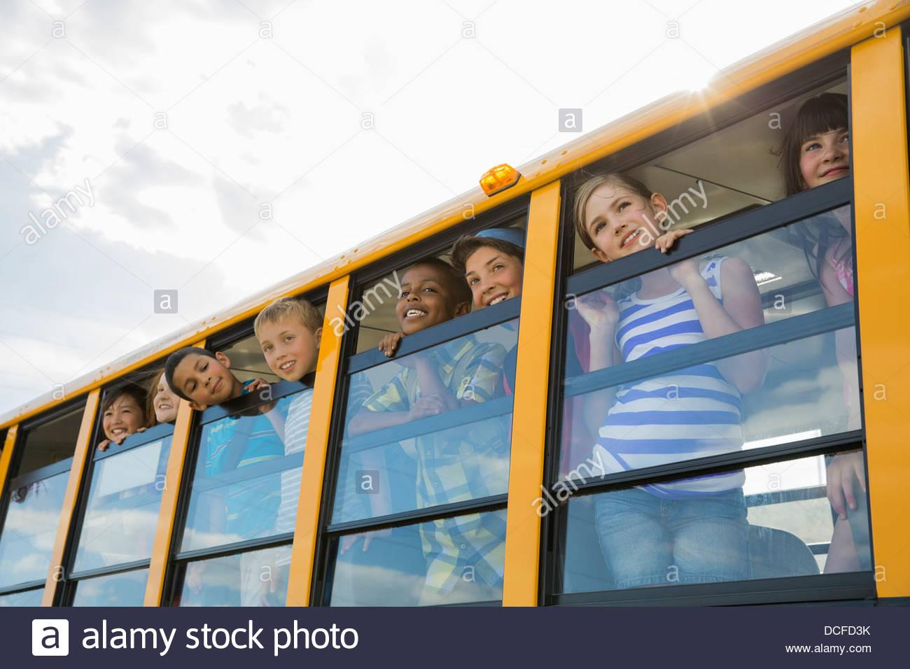 Group of schoolchildren looking through bus window - Stock Image